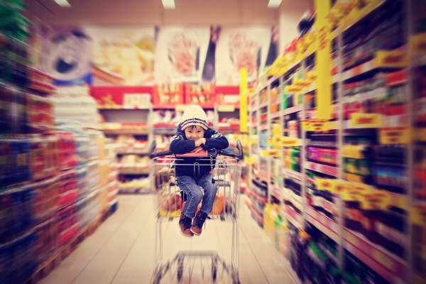 This is an image of a child in a shopping trolley