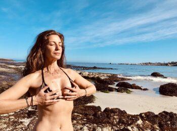 photo of lady in bikini holding breasts