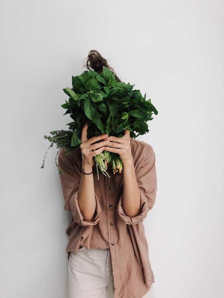 photo of lady covering face with greens